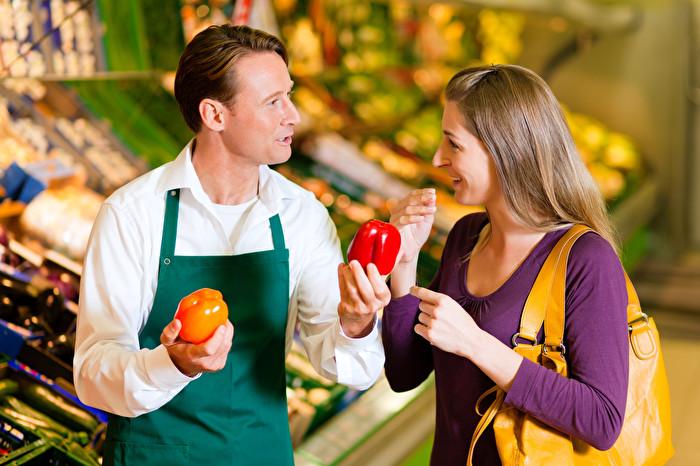 Frau im Supermarkt und Verkäufer